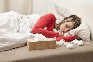 Woman Sick in Bed With Tissues