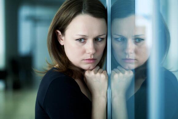Sad woman against window