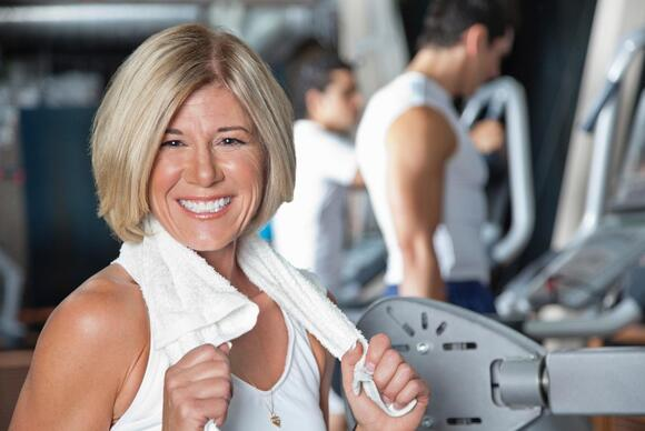 Mature adult with towel after working out at the gym