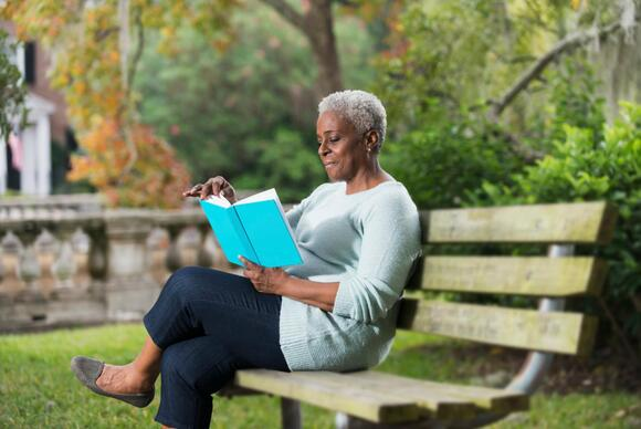 senior-african-american-woman-sitting-on-bench-reading