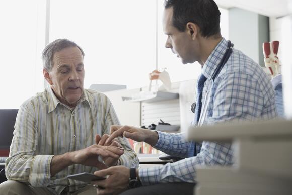 doctor examining male patient's hands