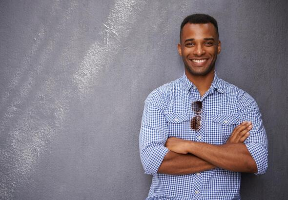 african-american-man-leaning-against-wall-smiling
