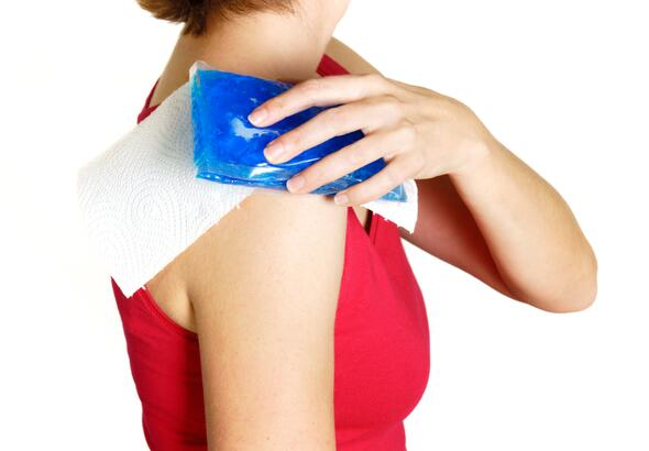 Woman holding ice pack on shoulder
