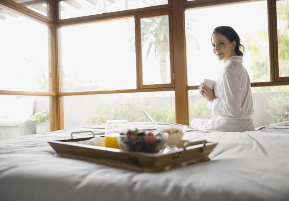 Woman sitting on bed holding coffee cup