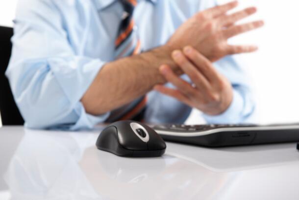 man touching wrist at desk