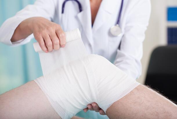 Doctor wrapping injured knee