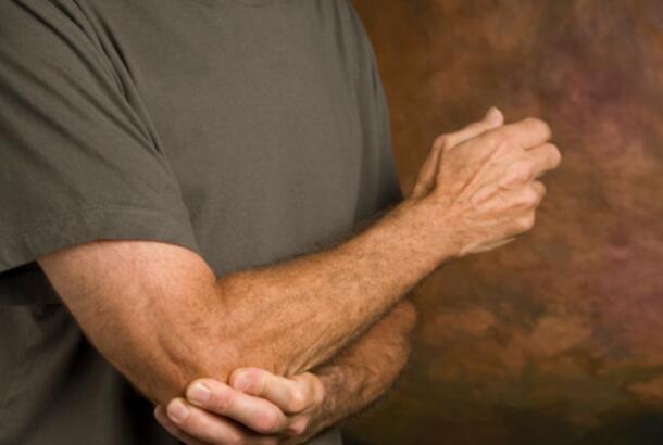 man holding elbow