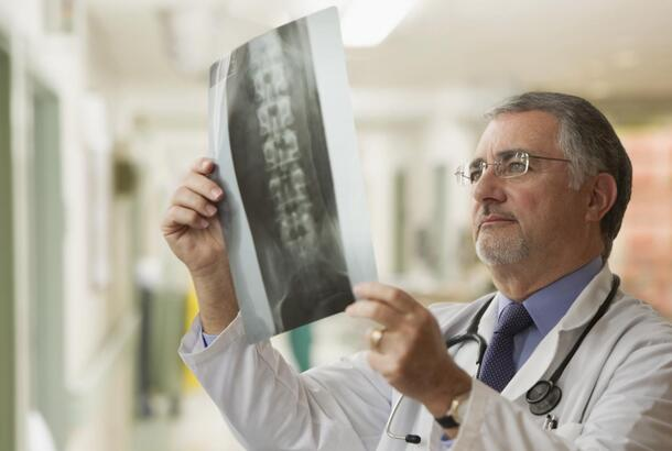 Elderly doctor looking at x-rays