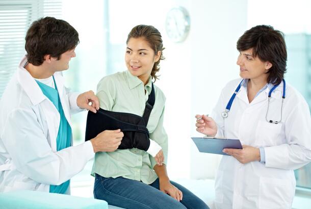 Doctor adjusting arm sling