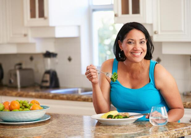 smiling woman eating food in kitchen
