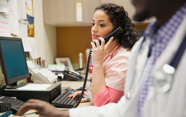 Female medical professional using telephone while working at desk with colleague in foreground