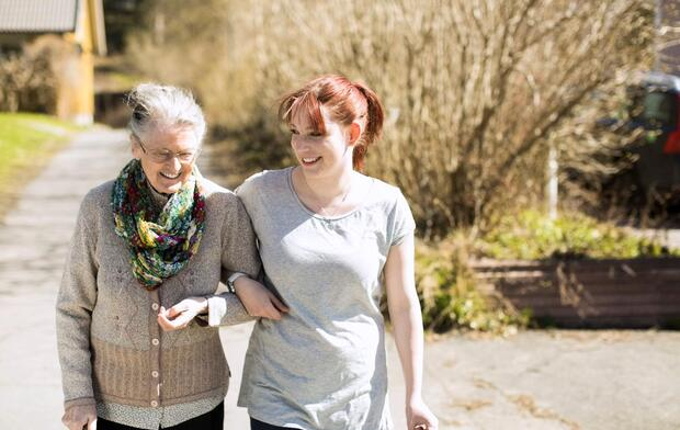 young female caregiver with senior patient