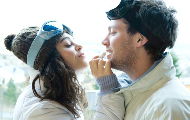 Woman applying lip balm to boyfriends lips