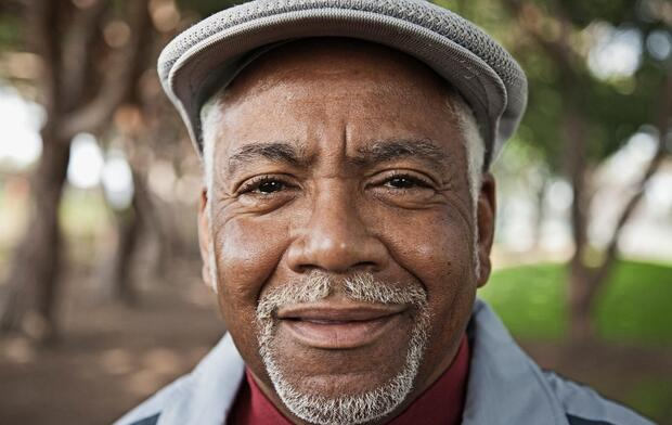 portrait of smiling senior African American man wearing hat