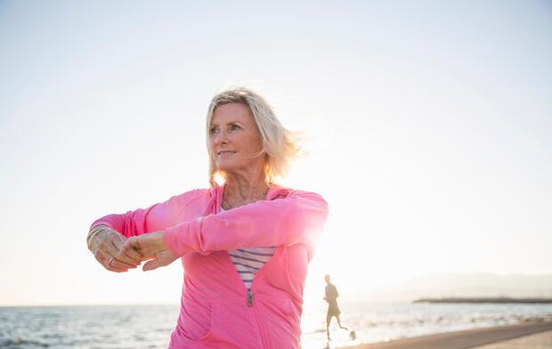 senior-woman-stretching-on-beach