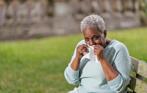 older woman wiping nose