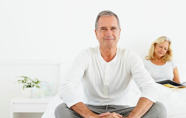 Senior man sitting on bed with woman at the back