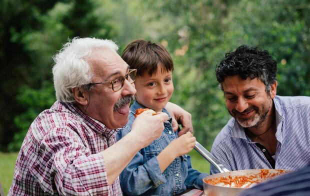 Senior man enjoying food with grandson and son