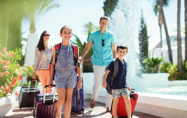 GettyImages-525408989-family-on-vacation-with-suitcases