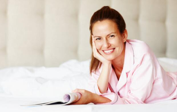 Smiling woman relaxing on bed