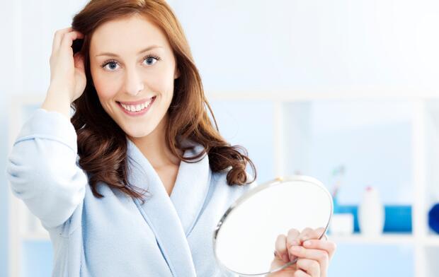 Women fixing hair in bathroom