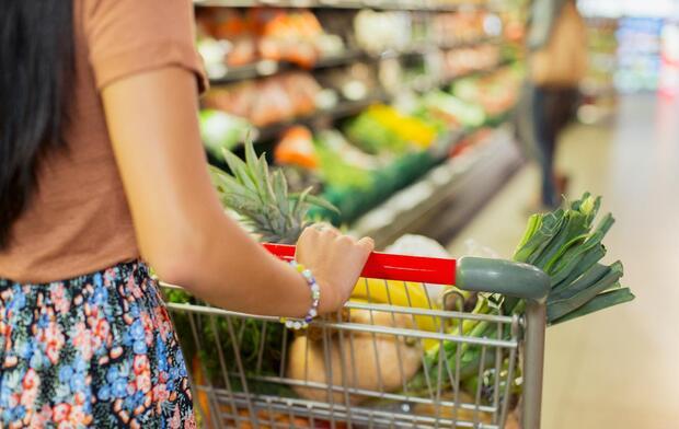 woman-pushing-cart-through-grocery-aisle