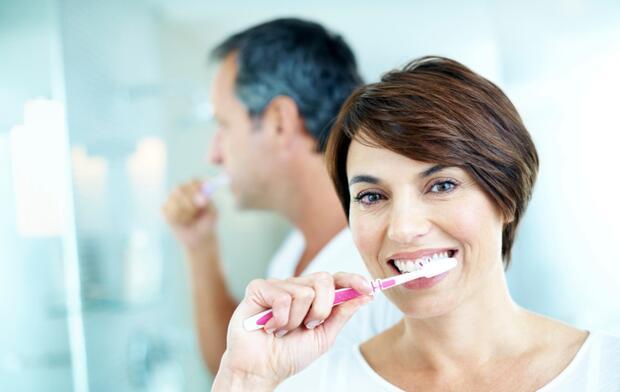 Man and women brushing teeth