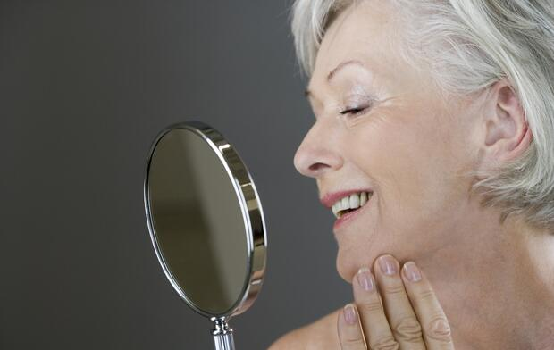 A senior woman looking at her face in the mirror