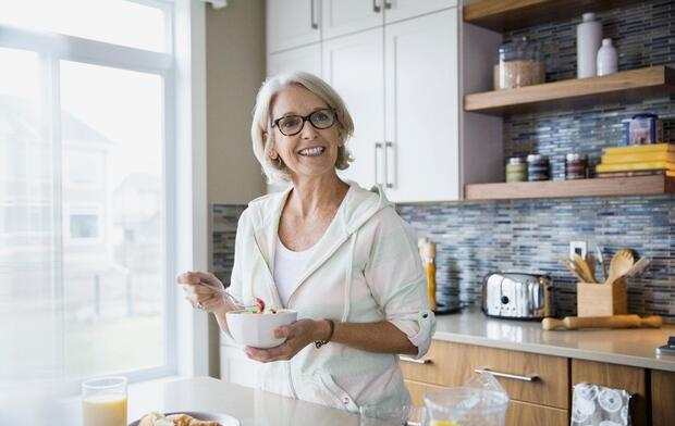 smiling senior woman eating breakfast at kitchen table