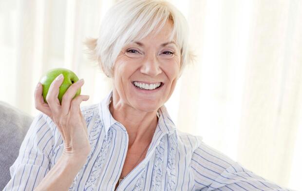 senior woman smiling holding apple