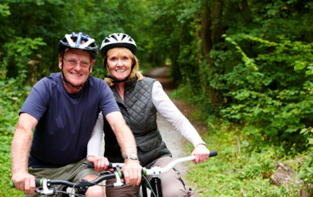 Couple riding bicycles pose for smile