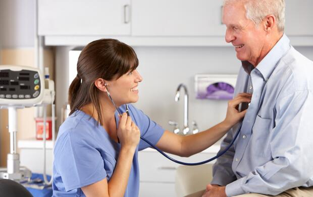 Women doctor checking heart of male patient