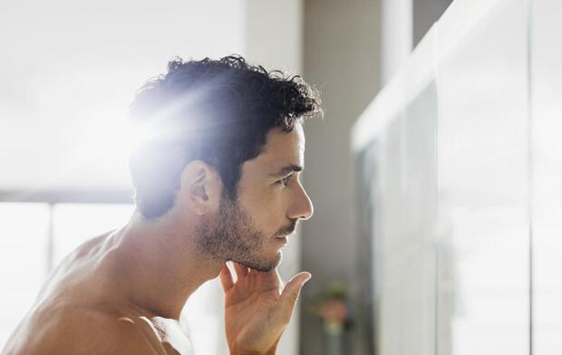 man checking face in mirror